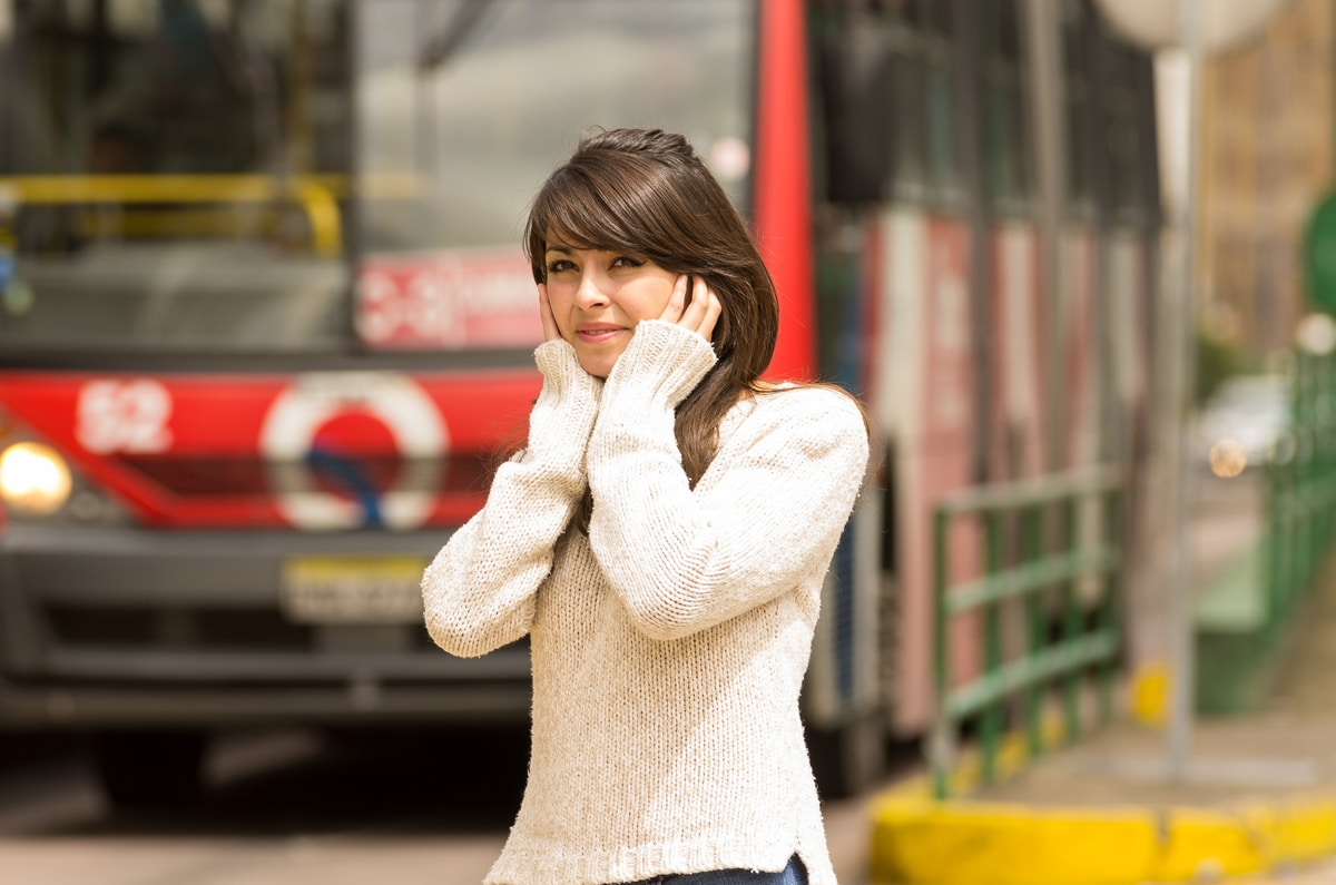 portrait of woman walking on the city street covering her ears concept of noise pollution
