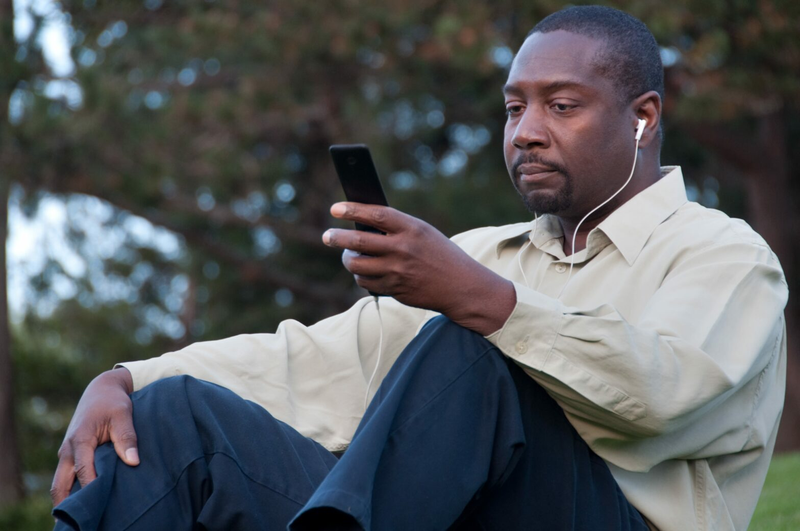 Man sitting with Apple earbuds in his ears